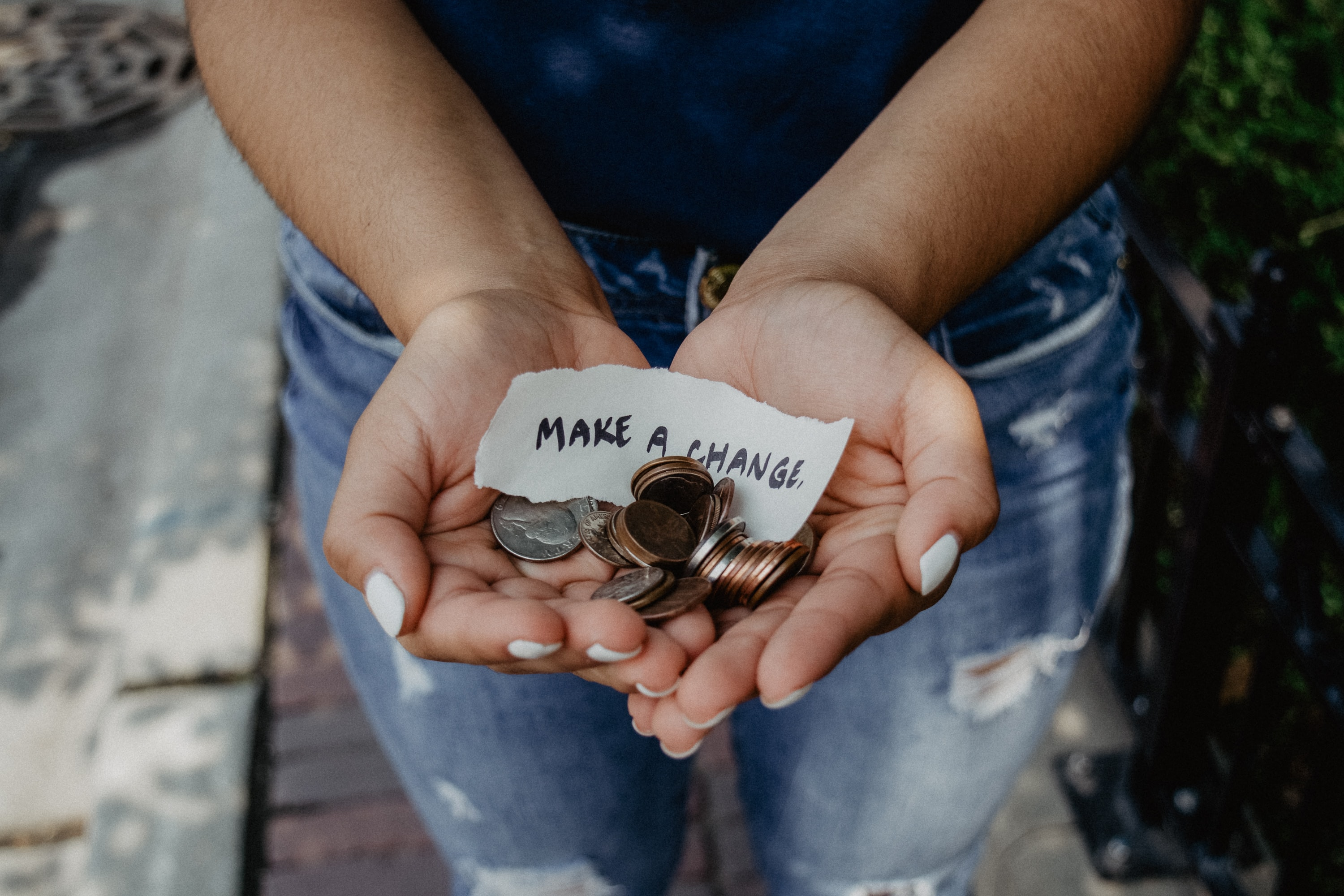 "Adult wearing all blue with white painted nails with open hands with change and a note that says ""MAKE A CHANGE""."